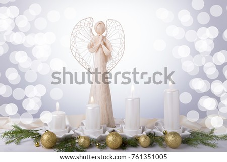 A white angel and four white Advent candles, Christmas tree branches are decorated with golden balls. The imminent background of Advent and Christmas #761351005
