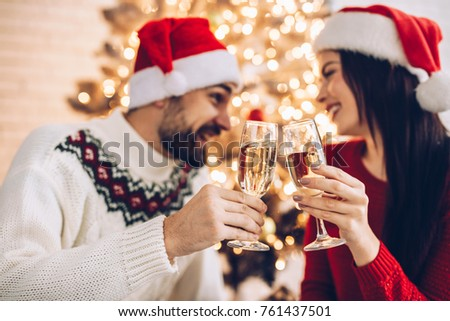Christmas couple cheers together near ornate festive Eve on Sata Claus hats. Holidays celebrations family  together #761437501