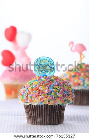 Colorful birthday cupcakes on white background