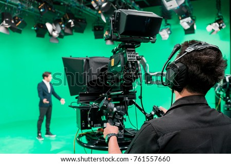 Cameraman working with announcer in broadcast television green screen studio room and professional camera.
