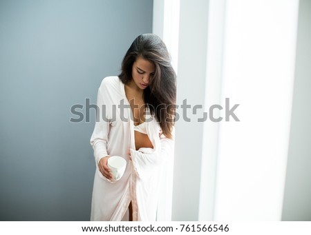 Portrait of young woman in lingerie standing in the room #761566546
