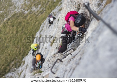 Woman and group of other people climbing on steep rock face on via ferrata. Climbers on via ferrata climbing route. Alpine ferrata ascent to summit. Summer adventure mountain activity. #761580970