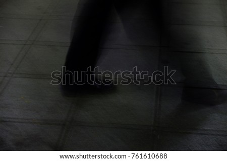 Person is walking on the street as blurred motion background, Focus at his legs concept #761610688