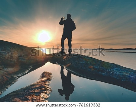 Rear silhouette of travelling man taking selfie at sea. Tourist with backpack standing on a rock, looking  over blue sea and taking photo by his smart phone camera #761619382