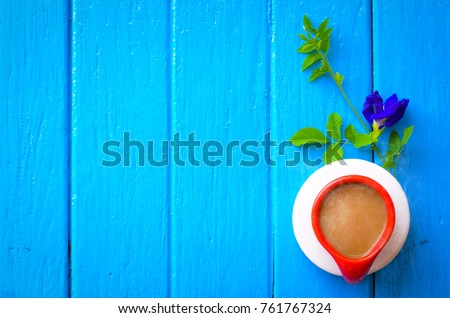 Good morning word, cup of coffee on blue background,top view ,empty space.