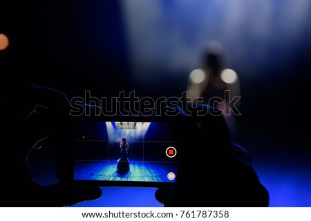 Hands with a smartphone records live music festival and taking photo of concert stage live concert luxury party in facebook live.