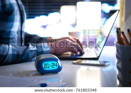 Man working late. Workaholic or being behind schedule concept. Business person in modern office building or home at night using laptop. Time in digital clock on table in workstation.  #761803348