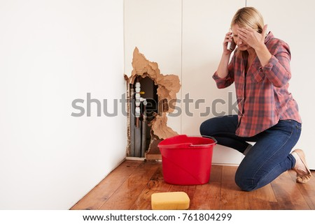 Middle aged woman with a burst water pipe phoning for help Royalty-Free Stock Photo #761804299