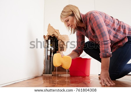 Worried woman mopping up water from a burst pipe with sponge Royalty-Free Stock Photo #761804308