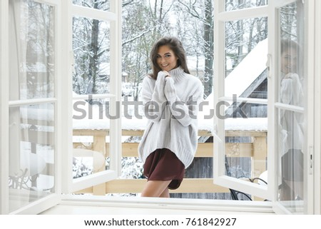 Happy woman is standing on the balcony at snowy winter day #761842927