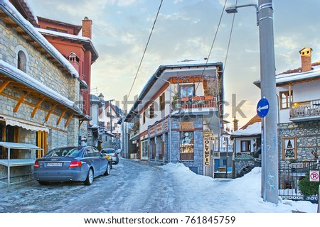 METSOVO, GREECE - JANUARY 2, 2012: The winding street of old town with traditional houses of Epirus region, multiple stores and hotels, on January 2 in Metsovo. #761845759