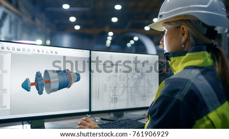 Inside the Heavy Industry Factory Female Industrial Engineer Works on the Personal Computer on the Turbine/ Engine Project in 3D Using CAD Program. #761906929