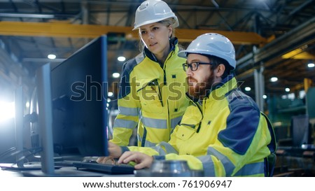 Male Industrial Engineer Works on the Personal Computer while Female Manager Talks about Project. They Work in Heavy Industry Manufacturing Factory. Royalty-Free Stock Photo #761906947