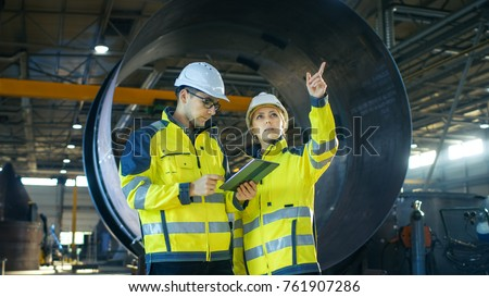 Male and Female Industrial Engineers Have Discussion while Using Tablet Computer. They Work in a Heavy Industry Manufacturing Factory. #761907286