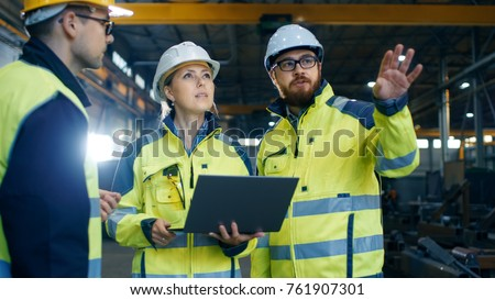 Male and Female Industrial Engineers Talk with Factory Worker while Using Laptop. They Work at the Heavy Industry Manufacturing Facility. #761907301