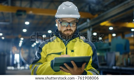 Industrial Engineer in Hard Hat Wearing Safety Jacket Uses Touchscreen Tablet Computer. He Works at the Heavy Industry Manufacturing Factory. #761908006