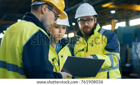 Three Industrial Engineers Talk with Factory Worker while Using Laptop. They Work at the Heavy Industry Manufacturing Facility. Royalty-Free Stock Photo #761908036