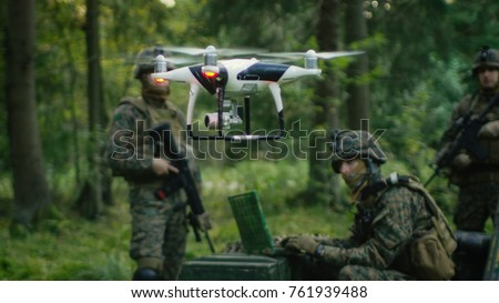 In the Military Staging Base Army Engineer and Soldiers Fly Military Grade Industrial Drone for their Reconnaisance/ Surveillance Mission/ Operation. Theater of Operation is in Forest Area. #761939488