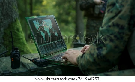 Military Operation in Action, Soldiers Using Military Grade Laptop Targeting Enemy with Satellite. In the Background Camouflaged Tent on the Forest. #761940757