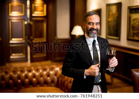 Handsome elegant businessman drinking red wine in bar #761948251