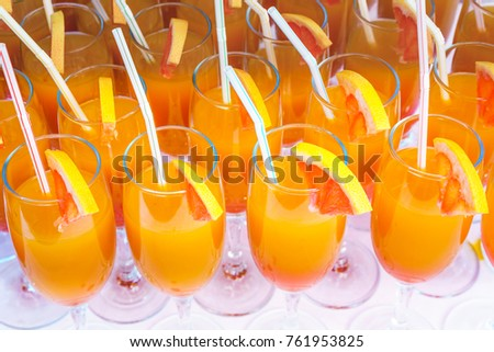 Orange juice cocktail in a flute glasses and slice of fresh orange with straw on white table, close picture.