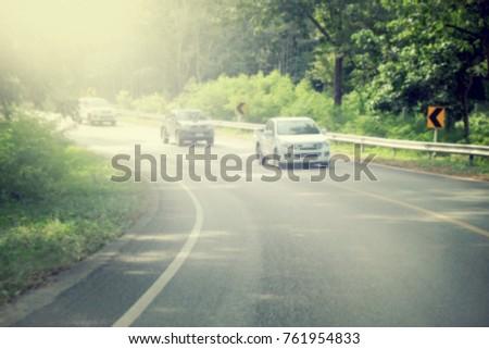 Asphalt road through the forest, blur natural background #761954833