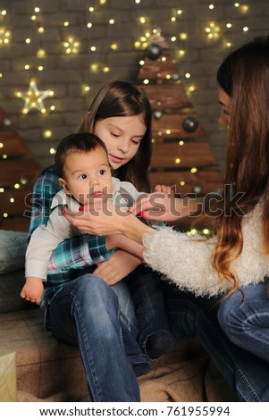 Mother with daughter and baby boy over Christmas Tree on Holiday theme #761955994