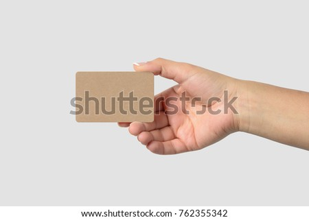 Mockup of female hand holding a Kraft Paper Business Card isolated on light grey background. Rounded corner, size 85 × 55 mm.