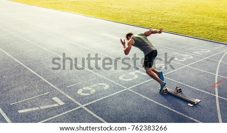 Rear view of an athlete starting his sprint on an all-weather running track. Runner using starting block to start his run on race track.