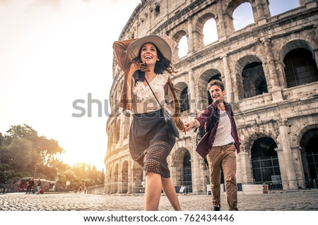 Young couple at the Colosseum, Rome - Happy tourists visiting italian famous landmarks Royalty-Free Stock Photo #762434446