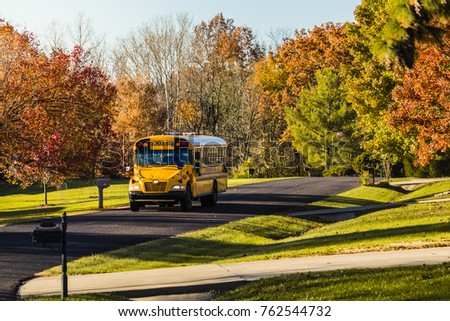 Yellow school bus driving along a suburban street in the fall; trees and the sky in the background; Missouri, Midwest #762544732