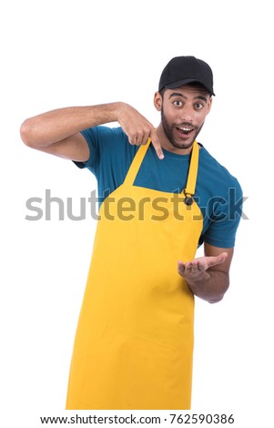 man wearing a black cap and yellow apron pointing at something he holds. Isolated on white background. #762590386