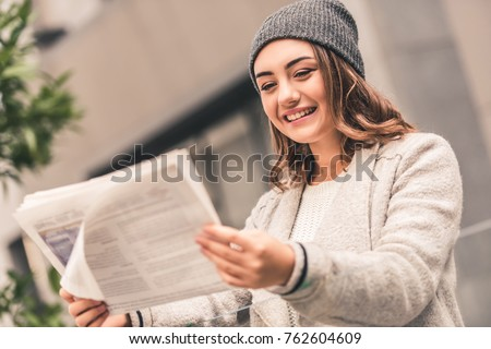 Beautiful girl in coat and cap is reading a newspaper and smiling while resting outdoors #762604609