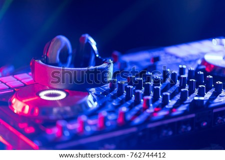 In selective focus of Pro dj controller.The DJ console cd mp4 deejay mixing desk Ibiza house music party in nightclub with colored disco lights. Royalty-Free Stock Photo #762744412