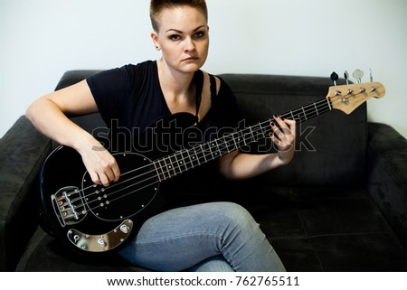 Woman musician with shot haircut with bass guitar at home #762765511