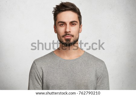 Isolated shot of young handsome male with beard, mustache and trendy hairdo, wears casual grey sweater, has serious expression as listens to interlocutor, poses in studio against white background #762790210