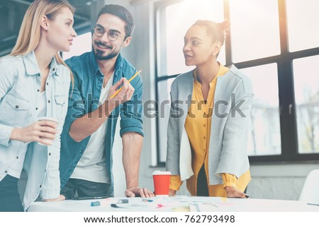 Team of successful young enterpreneurs discuss creative ideas for startup, think about pluses and minuses of investment money, prepare briefing for guests, stand at work place with hot coffee #762793498
