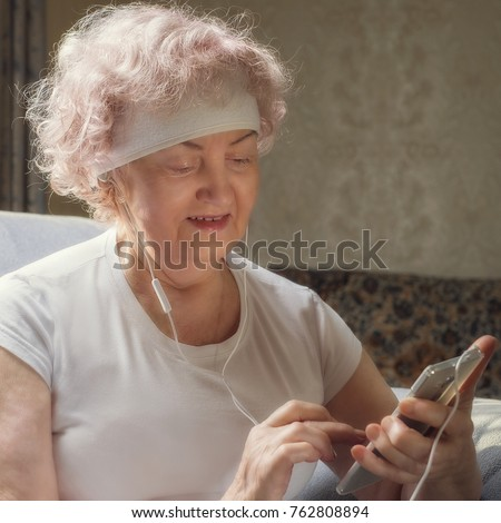 Elderly woman listening to music with a smile. Rest after fitness. #762808894