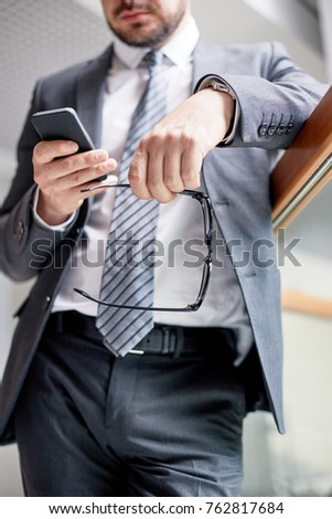 Close-up shot of unrecognizable entrepreneur with eyeglasses in hand standing at spacious office lobby and texting with colleague on smartphone #762817684