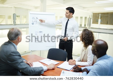 Young confident speaker pointing at financial data on whiteboard and explaining chart Royalty-Free Stock Photo #762830440
