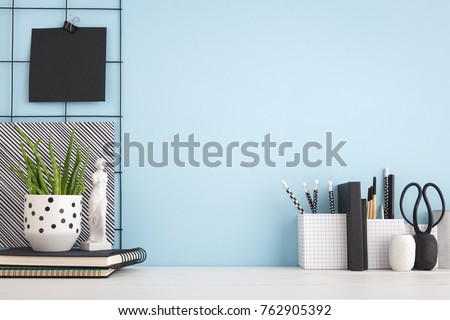 Office creative desk with supplies, and blue wall.  Royalty-Free Stock Photo #762905392