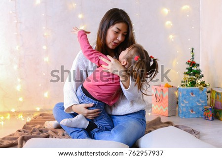 Beautiful girl and elder sister of small female child cares for younger sister and talks, fools around and laughs cute in family way, sitting on floor in bright room against backdrop of glowing #762957937