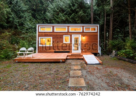 Small wooden cabin house in the evening. Exterior design. Royalty-Free Stock Photo #762974242