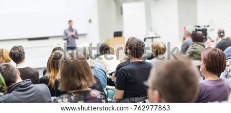 Male speaker giving presentation in lecture hall at university workshop. Audience in conference hall. Rear view of unrecognized participant in audience. Scientific conference event. #762977863