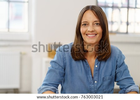 Happy businesswoman with a beaming friendly warm smile sitting at a desk in the office in a close up portrait #763003021
