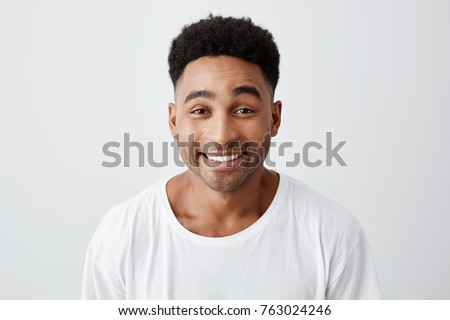 Close up isolated portrait of cheerful happy young man with afro hairstyle in casual white t-shirt smiling brightly, looking in camera with excited and joyful expression. #763024246