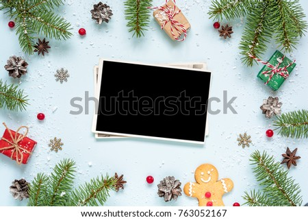 christmas blank photo card in frame made of fir tree branches, decorations and gift boxes over blue background. mock up. flat lay. top view