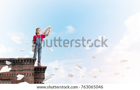 Cute happy kid girl on building top playing with paper plane #763065046