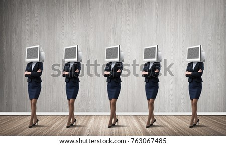 Business women in suits with monitors instead of their heads keeping arms crossed while standing in a row in empty room with gray wall on background. #763067485