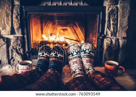 Feet in woollen socks by the Christmas fireplace. Couple sitting under the blanket, relaxes by warm fire and warming up their feet in woollen socks. Winter and Christmas holidays concept. #763093549